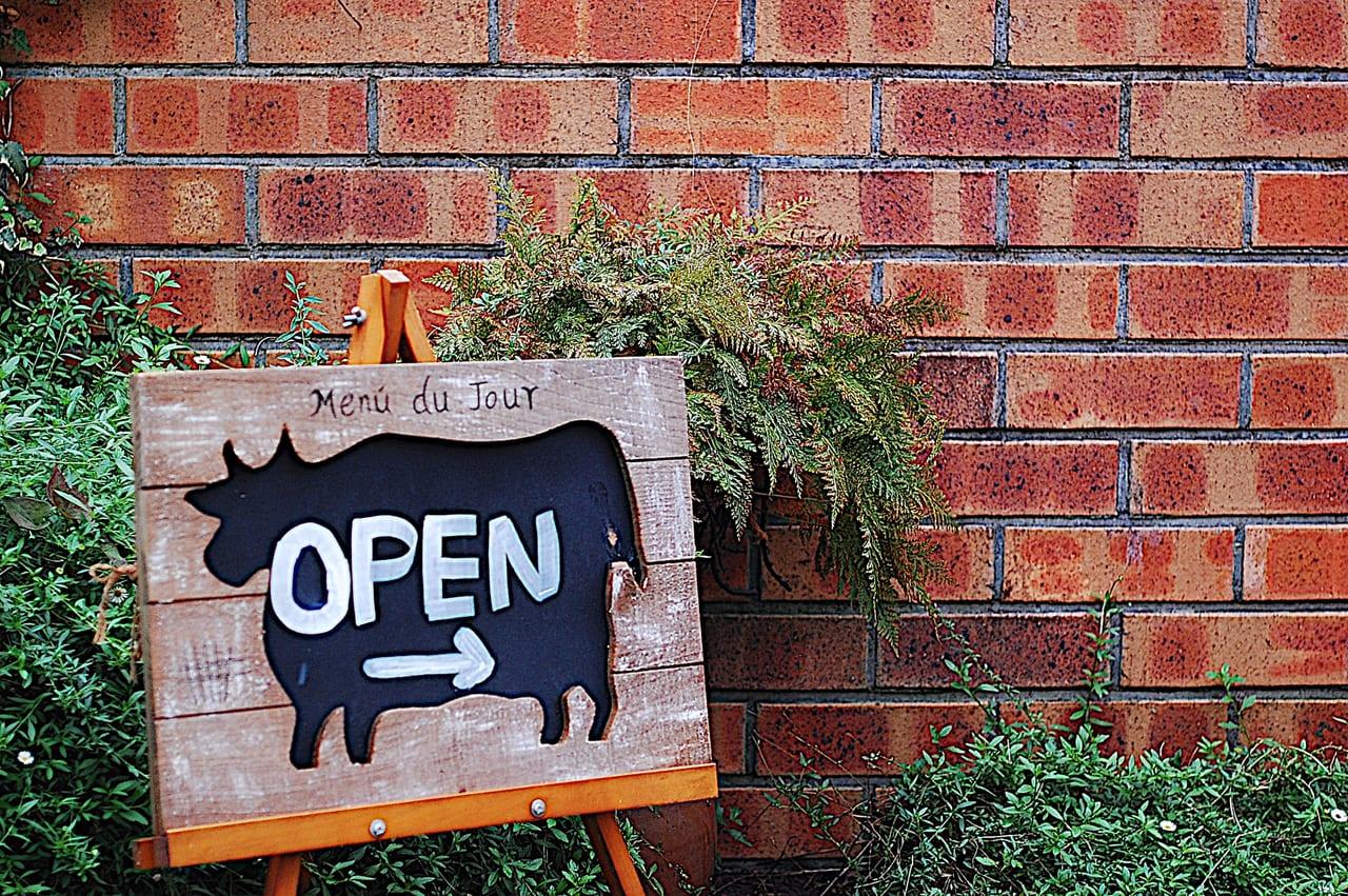 レンガ背景の牛のOPEN看板